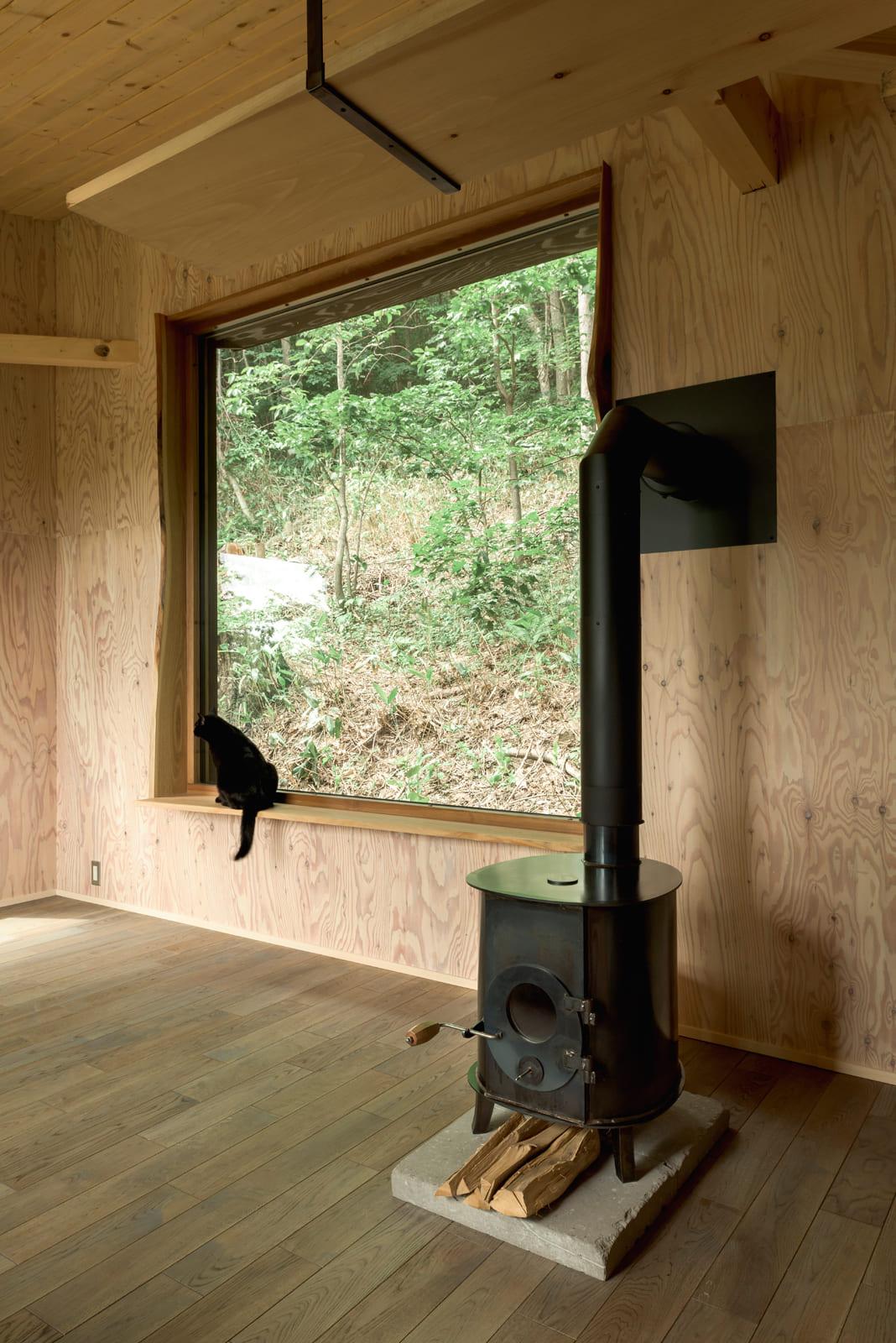 材本来の曲線や樹皮を意匠として生かして付けた窓枠に座っている猫