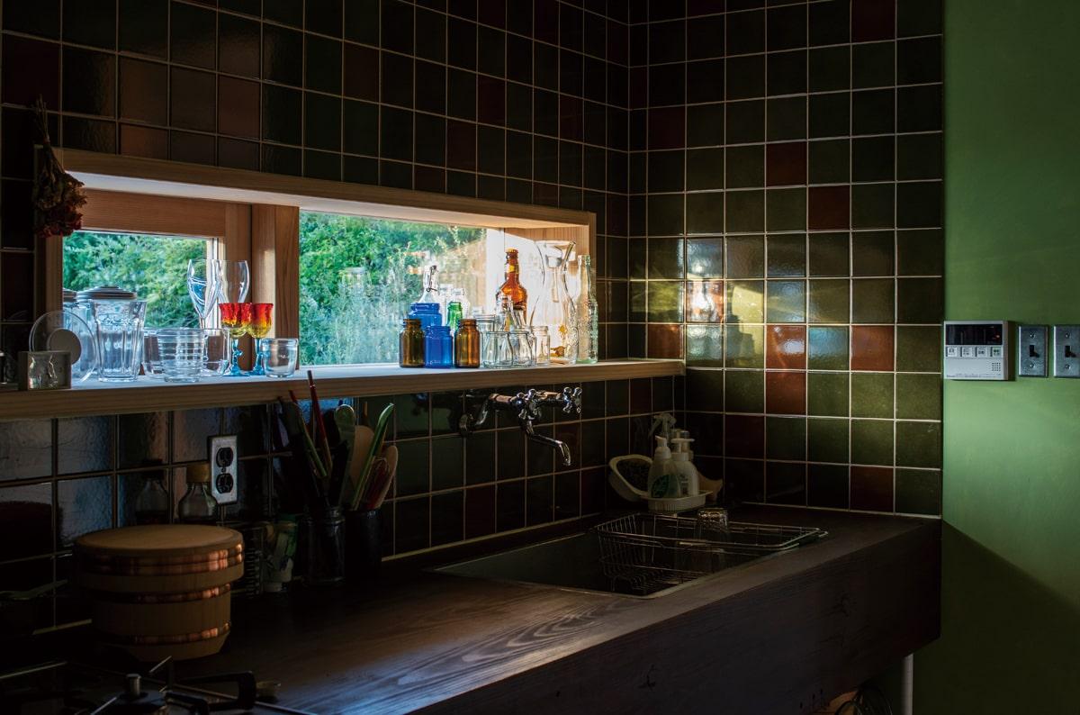 キッチンのシックなタイルはLIXILのショールームで一目惚れ。窓辺にはお気に入りのガラス類を飾っている