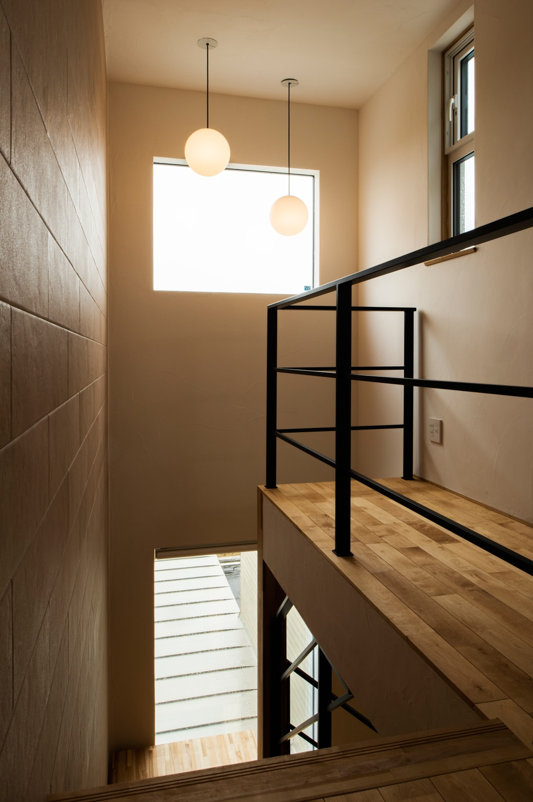 大きな窓から踊り場に光が降り注ぐ。壁は3階天井までエコカラット仕様。この階段が外からも見えるようにデザインした