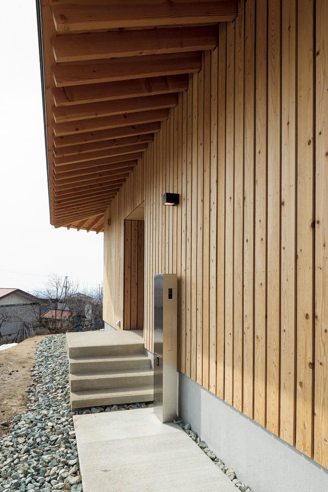 外壁は海外製の分厚い透湿防水シートの上に屋久島地スギのすのこ張りで、経年変化も楽しめる仕上げとしている。床面は積雪や眺望も考慮して基礎から持ち上げられているため、玄関へのアプローチは階段に