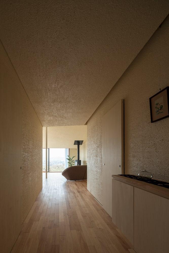 玄関から一直線に伸びるリビング・ダイニングへの動線は、劇的な眺望を演出する仕掛けにもなっている