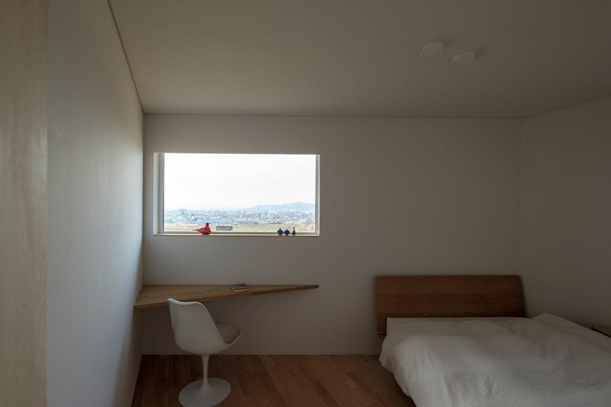 リビングの隣にある寝室からも山並みが見えるよう小窓を設けた。切り取られた風景が美しく空間に映える