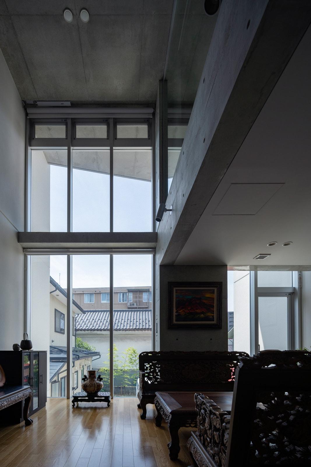 吹き抜けいっぱいに設けた大迫力のカーテンウォールで、応接室兼リビングは明るく伸びやかな空間に。吹き抜け最上部の外倒し窓が重力換気を促し、室内に外気を呼び込む