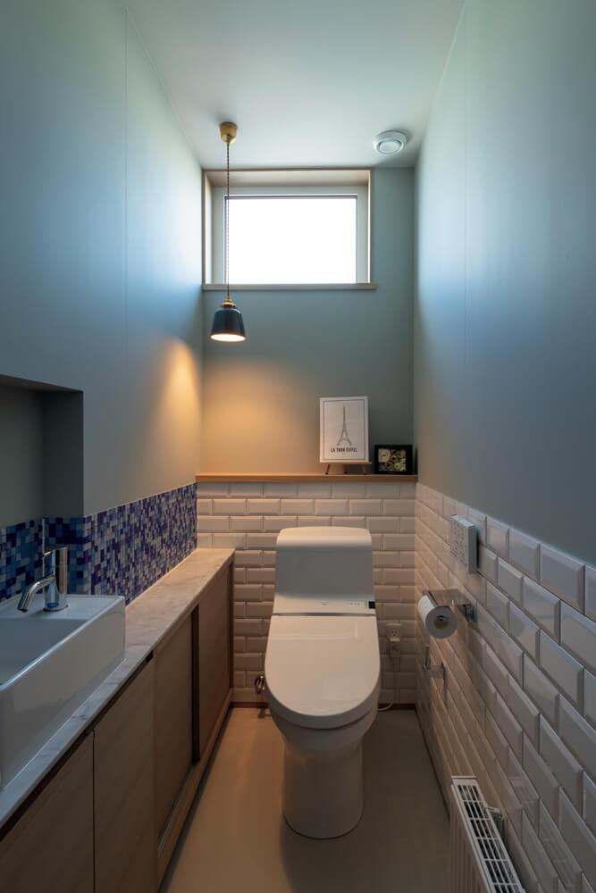 玄関の近くに配されたブルートーンのモザイクタイルがアクセントになっているトイレ