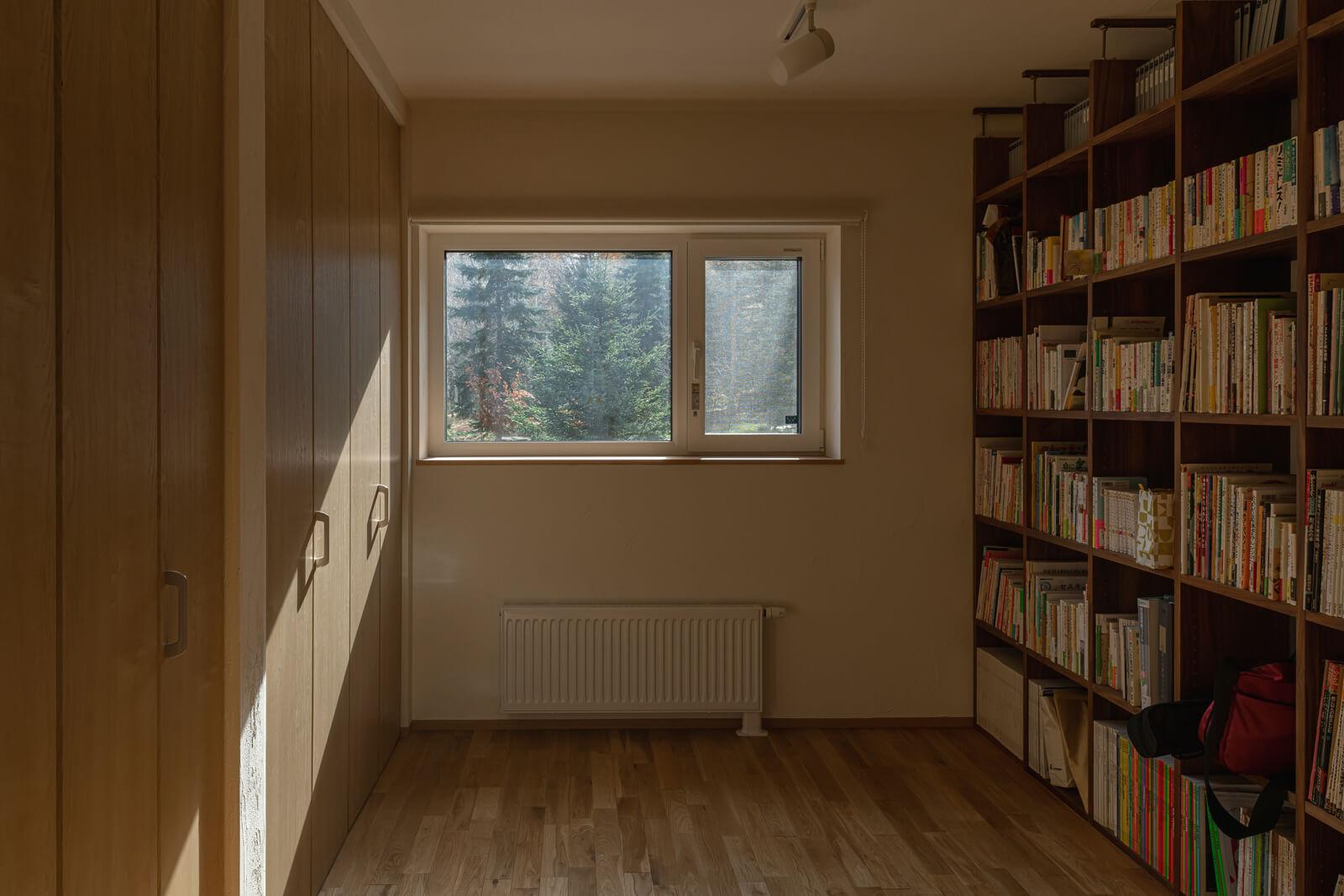 主寝室には、壁一面の蔵書。収納式のベッドで、日中はすっきりと