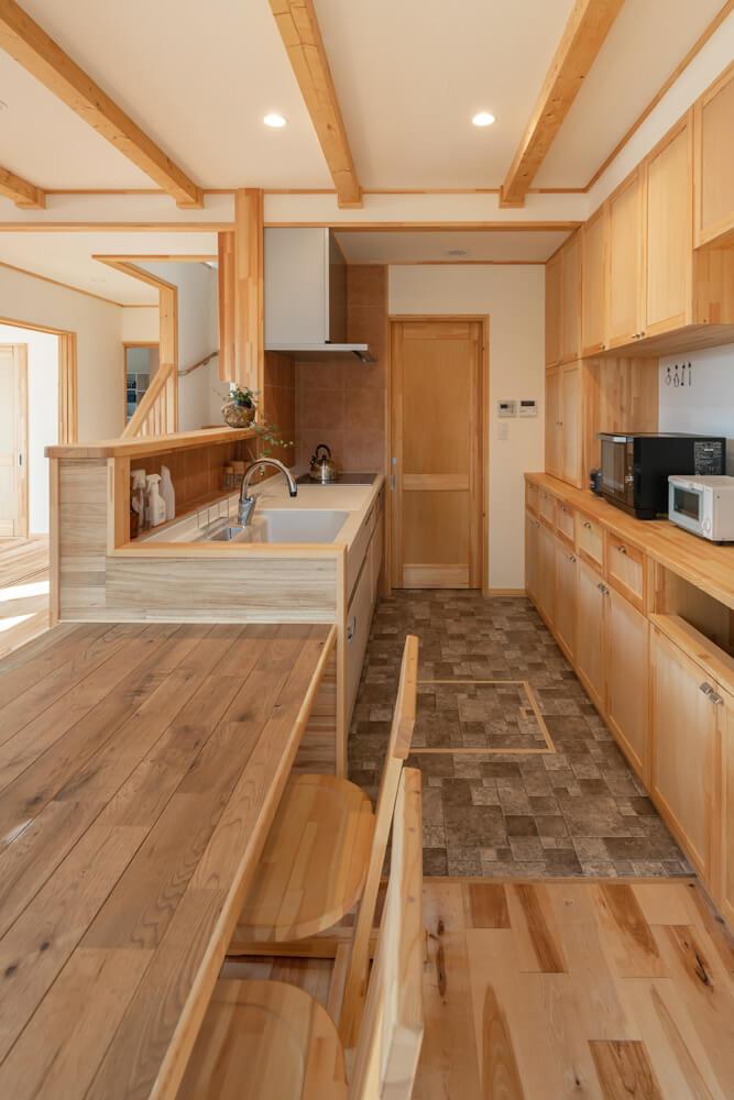 造作収納に加え、キッチンの床と壁面にはタイルを採用し、実用性をさらに高めた。奥はユーティリティ