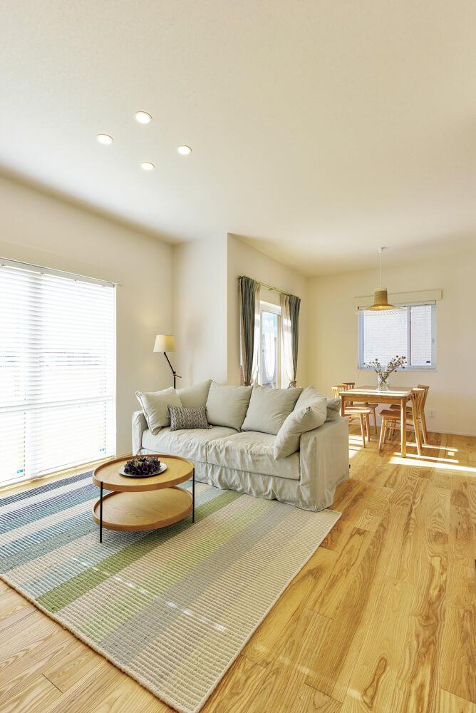 白い空間にタモの無垢床が映えるLDK。天井高があるため、実際の帖数よりも広く感じられる。1階フロアは床下エアコン1台で快適な室温に保たれている