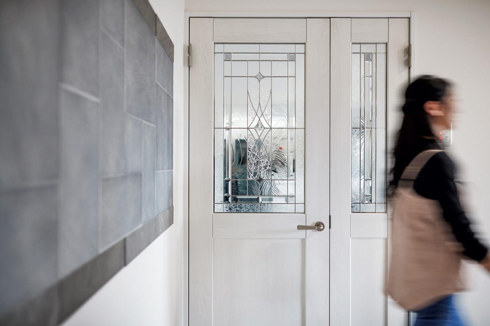 ステンドグラスのドアは、リビングの気配を自然に滲ませている。玄関でフェレットを飼っているため、左手の壁はエコカラットを採用。デザインのアクセントにもなっている