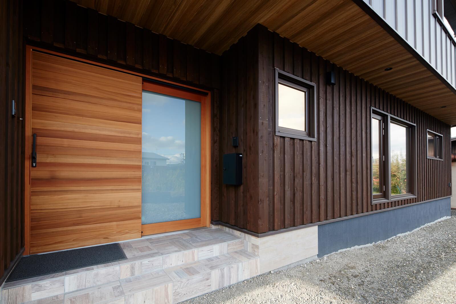 重厚感と木の優しさを兼ね備えた存在感のある玄関の大きな木製引き戸はHさんのお気に入り