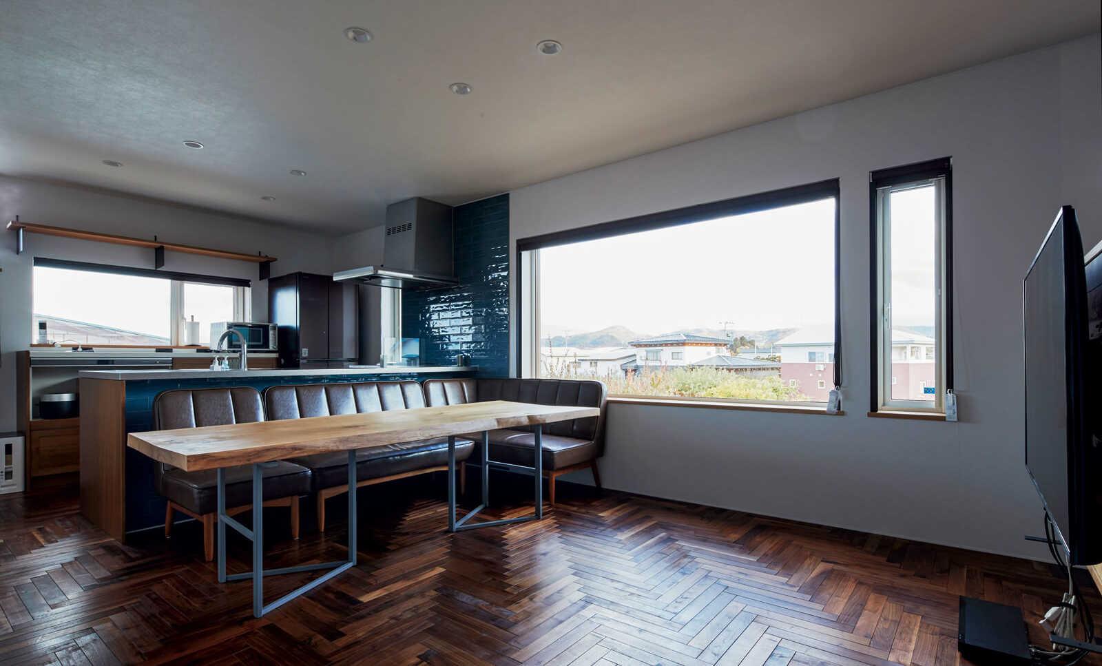 ヘリンボーン張りの無垢床が上質な雰囲気を漂わせる2階リビングは、大窓はもちろんキッチン奥の窓からも陽が射すのでいつも明るい