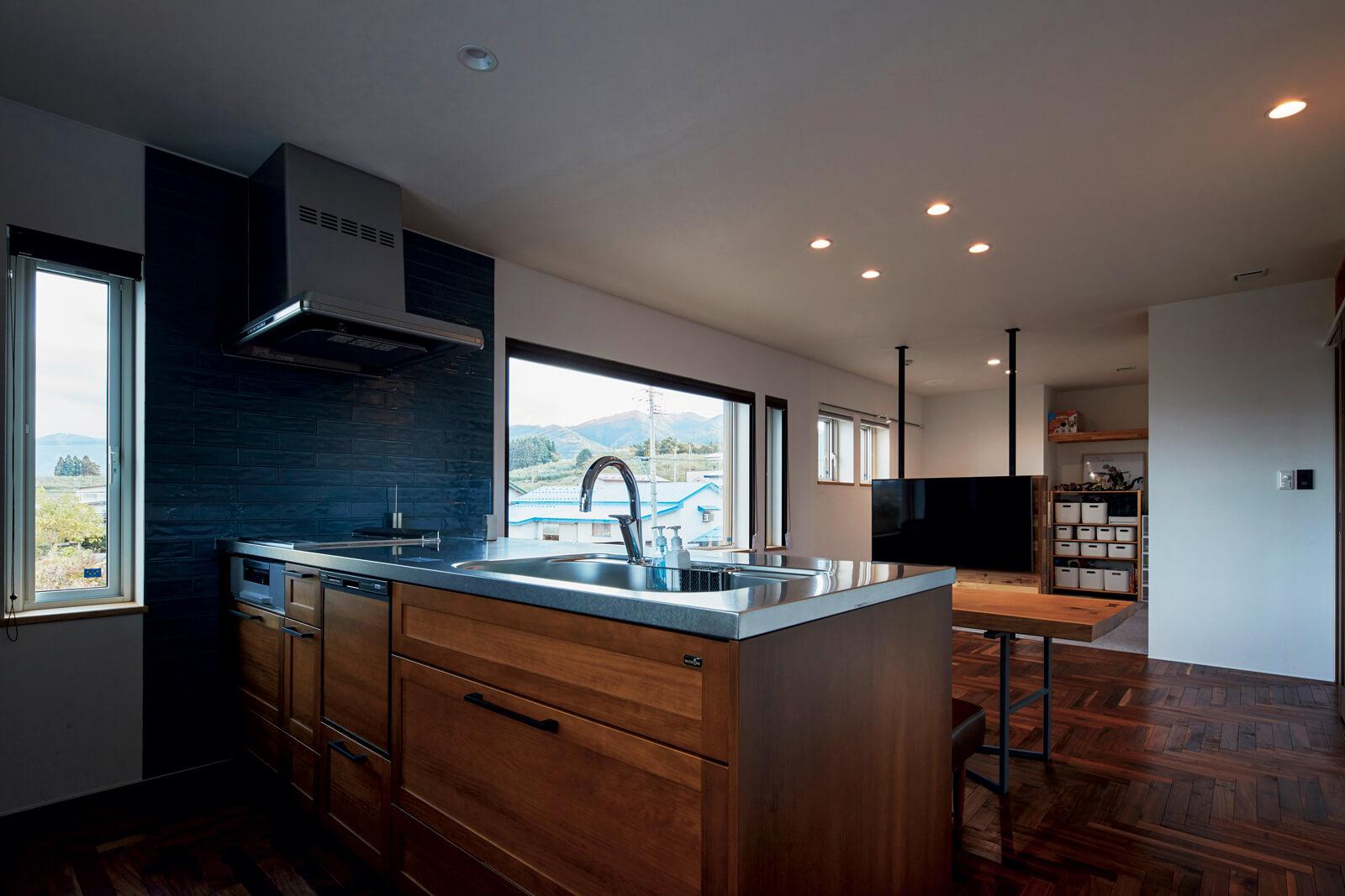 キッチンの面材も木を選んで空間に統一感を与えた。リビングのテレビの奥は、将来子ども部屋として区切る予定
