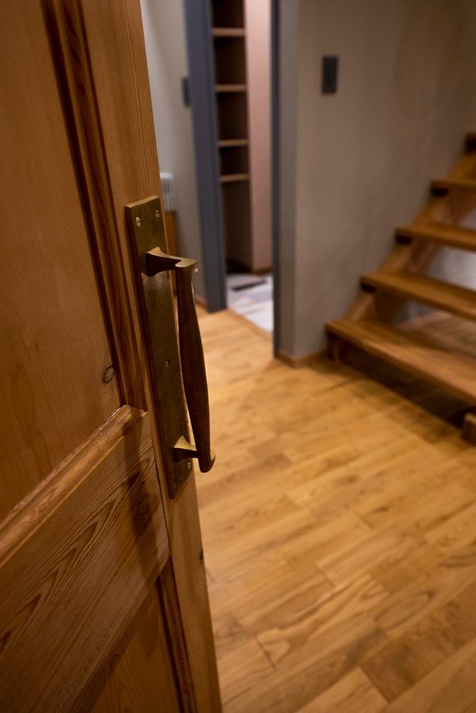 造作の扉には、経年変化が楽しめる真鍮製のドアハンドル