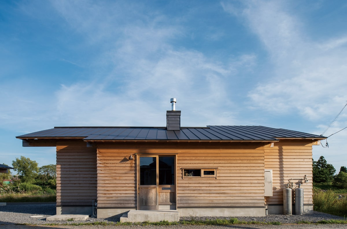 公道と住宅街に面している北向きの玄関側は、プライバシー保護と寒さ対策のため、開口部を抑えめに。外壁は無塗装のスギ材