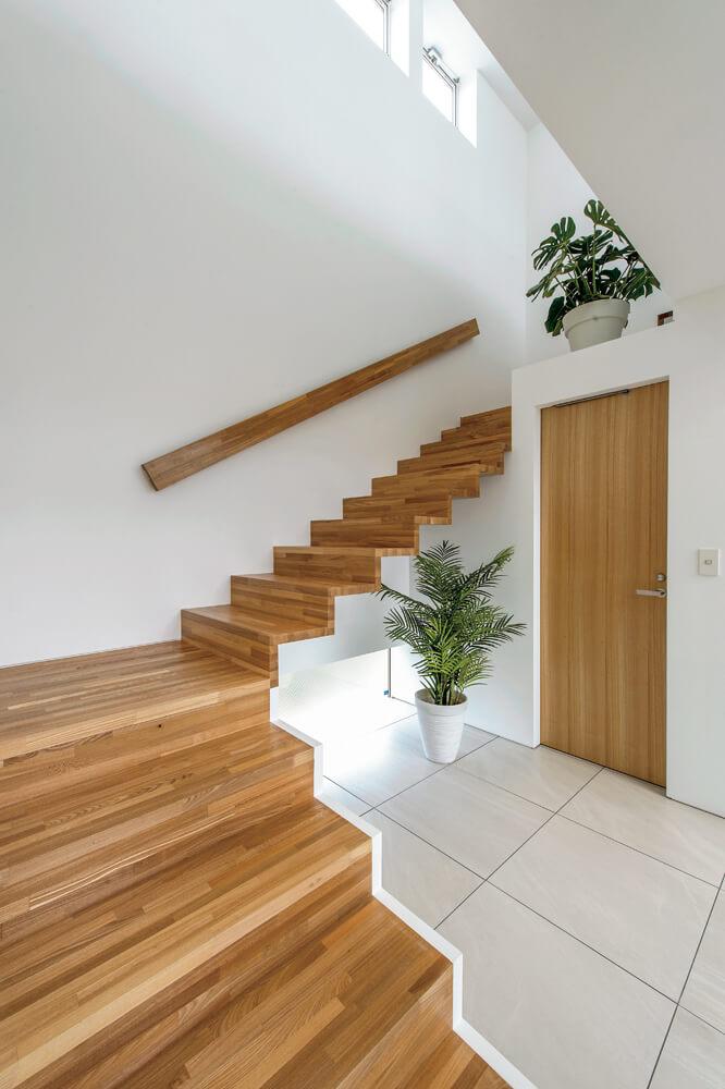 白い壁や床と木目のコントラストが美しい中折れの階段