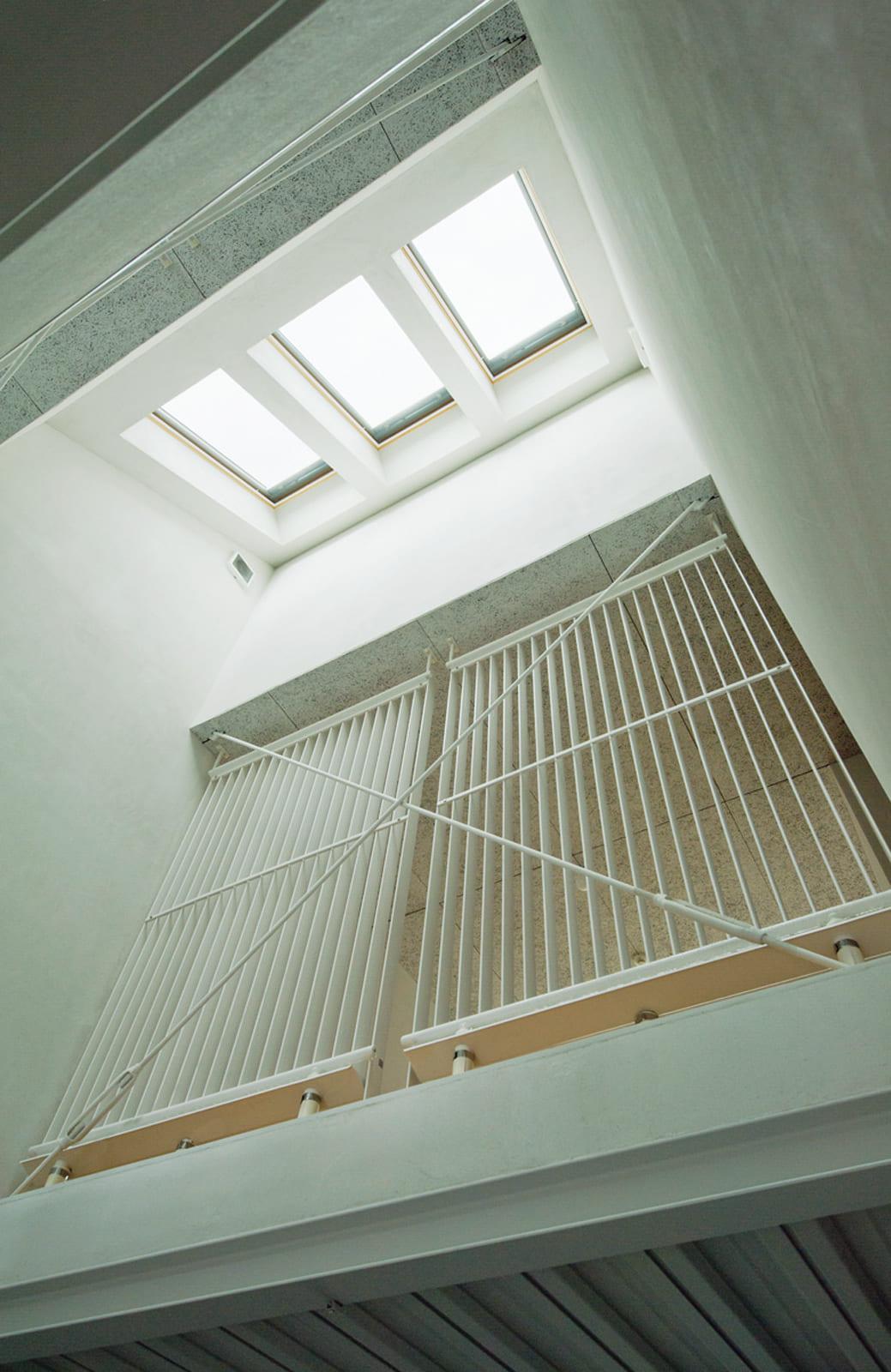 2階、細長い建物の中間にある吹き抜けは、開閉可能な天窓で採光と通風を確保した