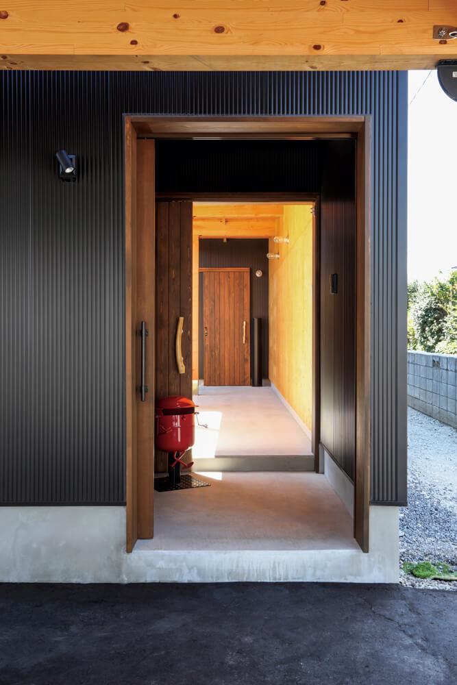 引き戸を開けると前室、屋根付きのアプローチを経て玄関へと通じている。造作引き戸には青森ヒバを使用