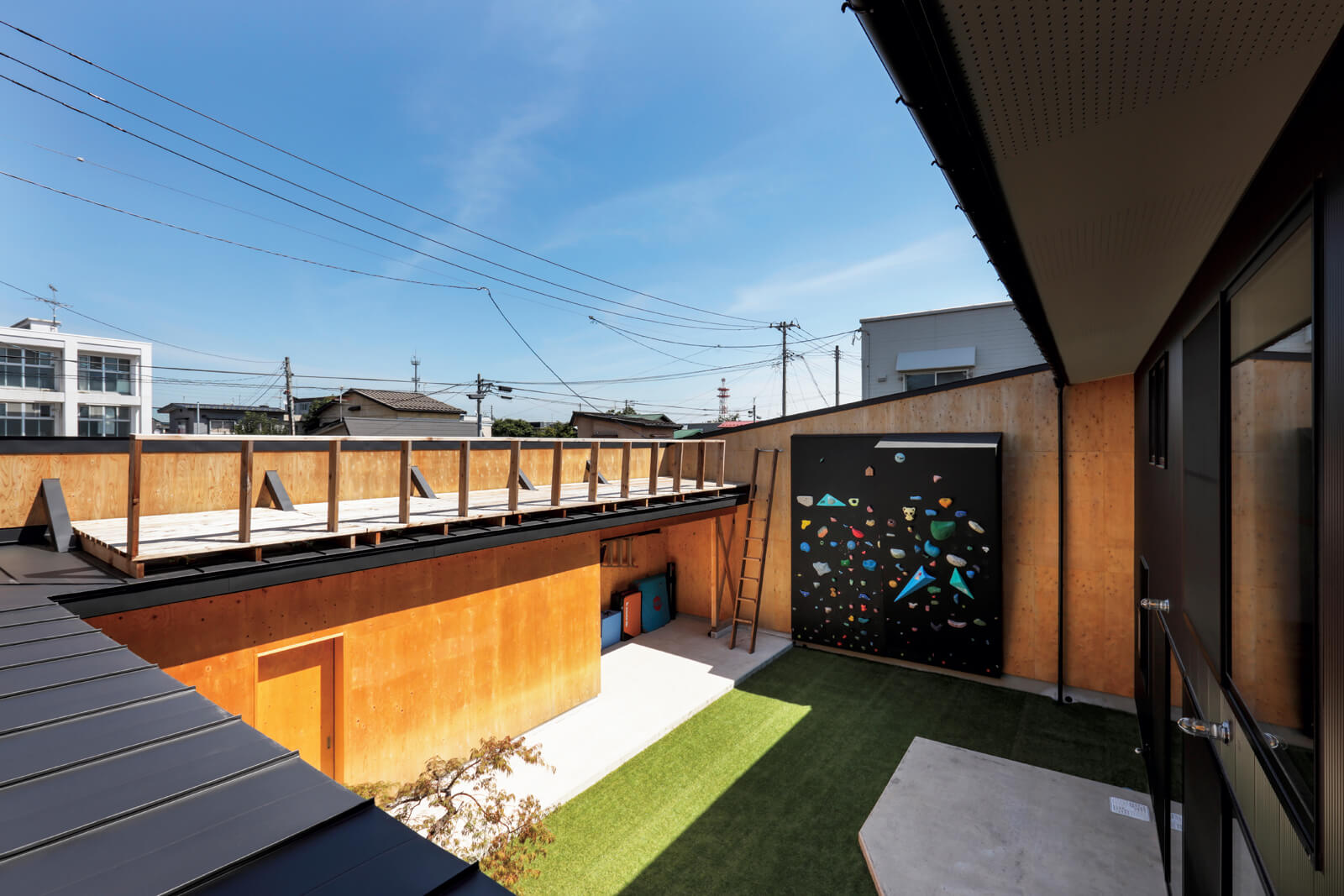 四方を建物や壁で囲まれた広い中庭にはボルダリングも。前室や外部収納の上部にはテラスが設けられ、積雪時には高低差を活かしてスキーやそり遊びもできる
