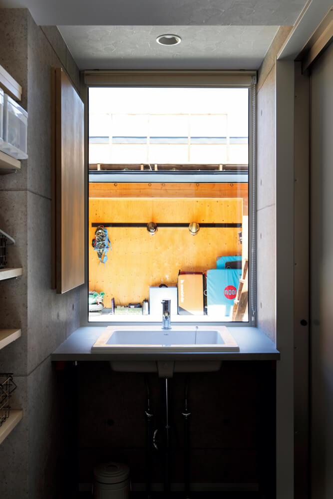洗面台の正面にも中庭に向いた窓を配置。普段室内で行われる生活行為が自然に外にあふれていく住まいだ