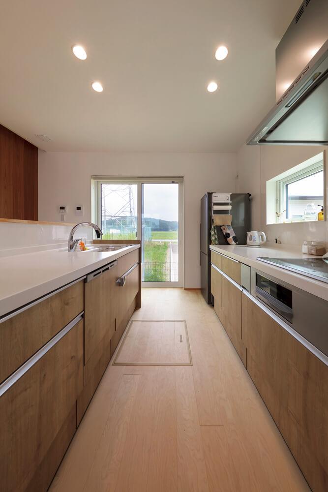 キッチンは2way動線のアイランド型。あえて北側開口として風景を取り込んだ。掃き出し窓は勝手口としても便利