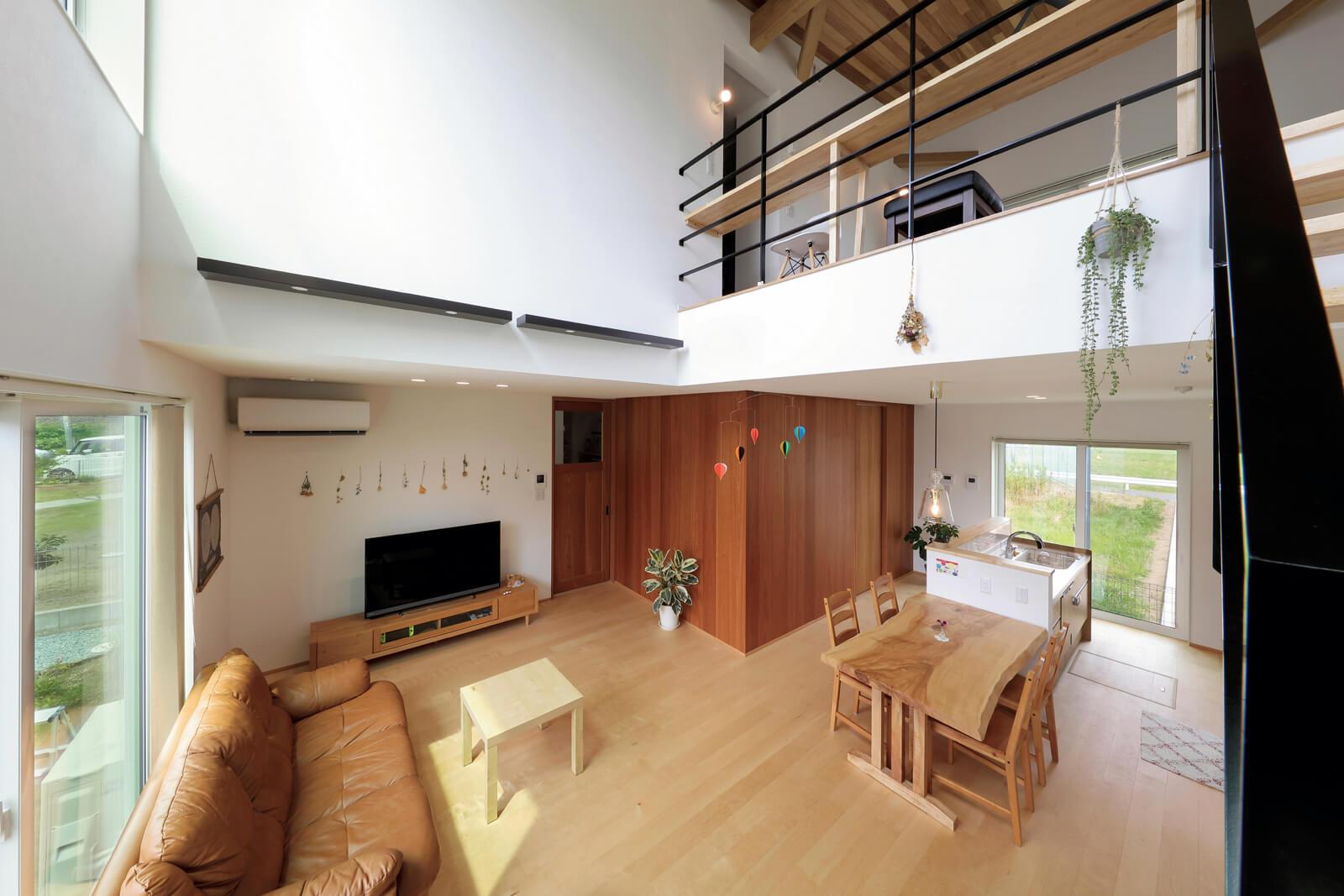 開放感と一体感が生まれる吹き抜けと階段。コーナー壁は建具と同系色のブラックチェリー材。板張り天井はレッドシダー