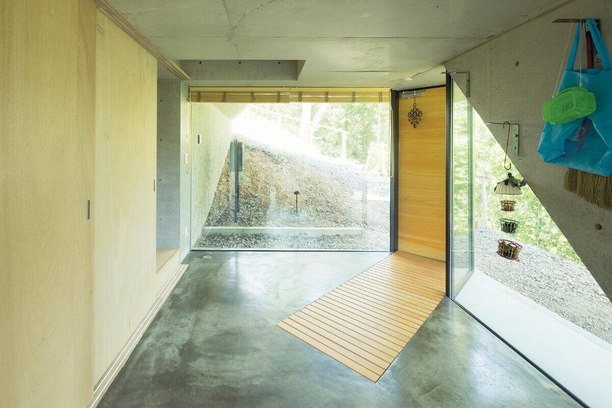 建物横の緩やかな階段を降りると、ガラス張りで明るい玄関。地下は玄関と寝室のみで、ほかの部屋はすべて2階に配置