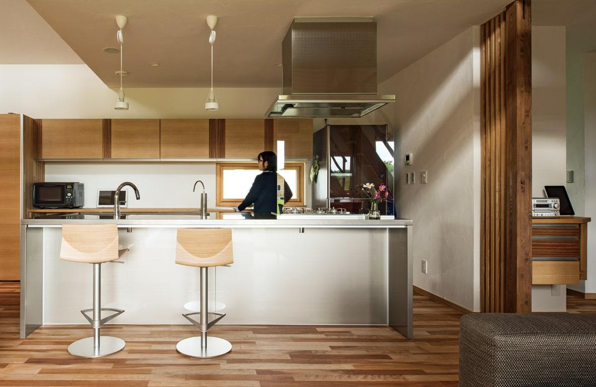 会話が途絶えることなく作業ができるアイランド型キッチン。キッチンをはじめとする随所に、キクザワならではの木を生かした造作収納・建具が配されている