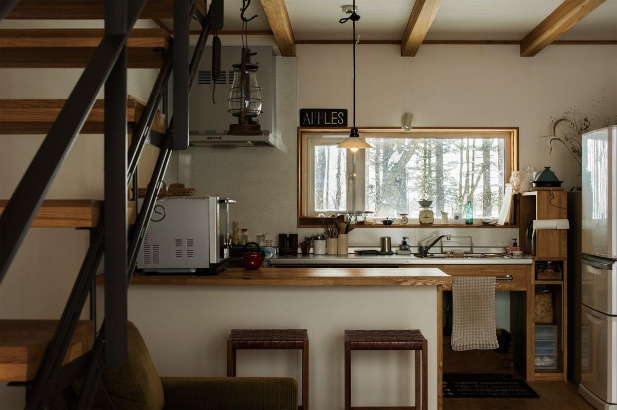 防風林を眺めながら家事ができるキッチンは、使い勝手に合わせて造作。古材を用いたカウンター裏も、収納棚になっている