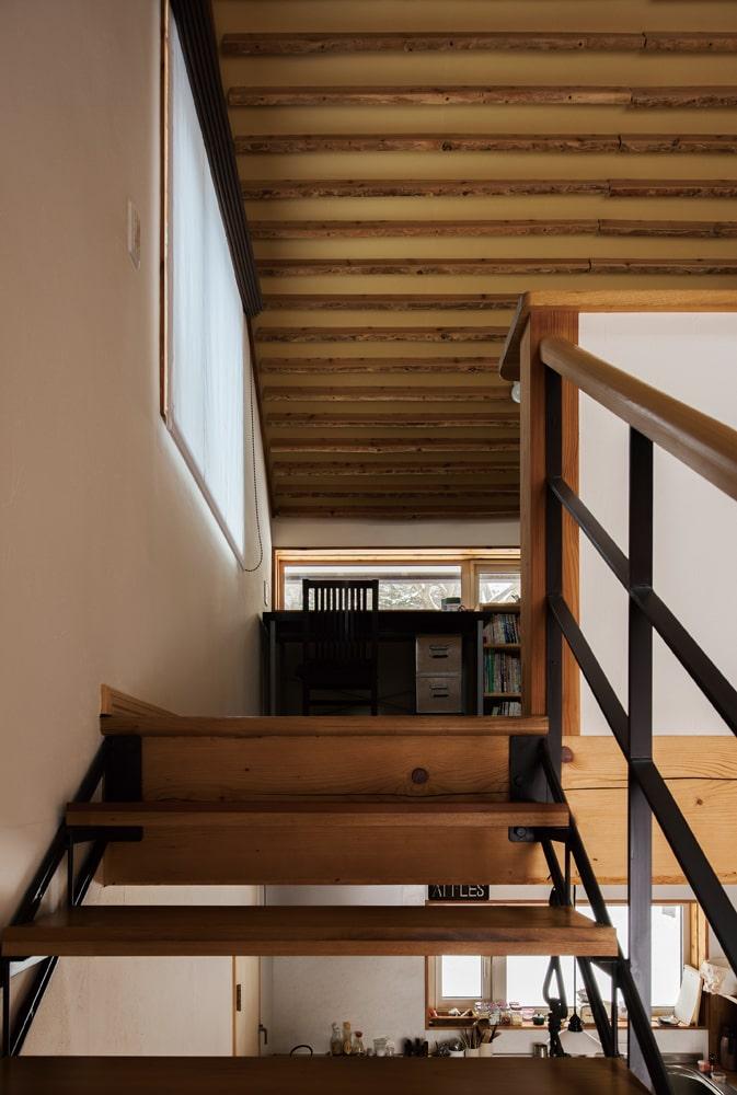 階段の踏板はセンやタモ、カツラ、ナラなどの古材。手すりにはヒノキを採用。天井には間伐材の耳付きカラマツを活用したルーバーを