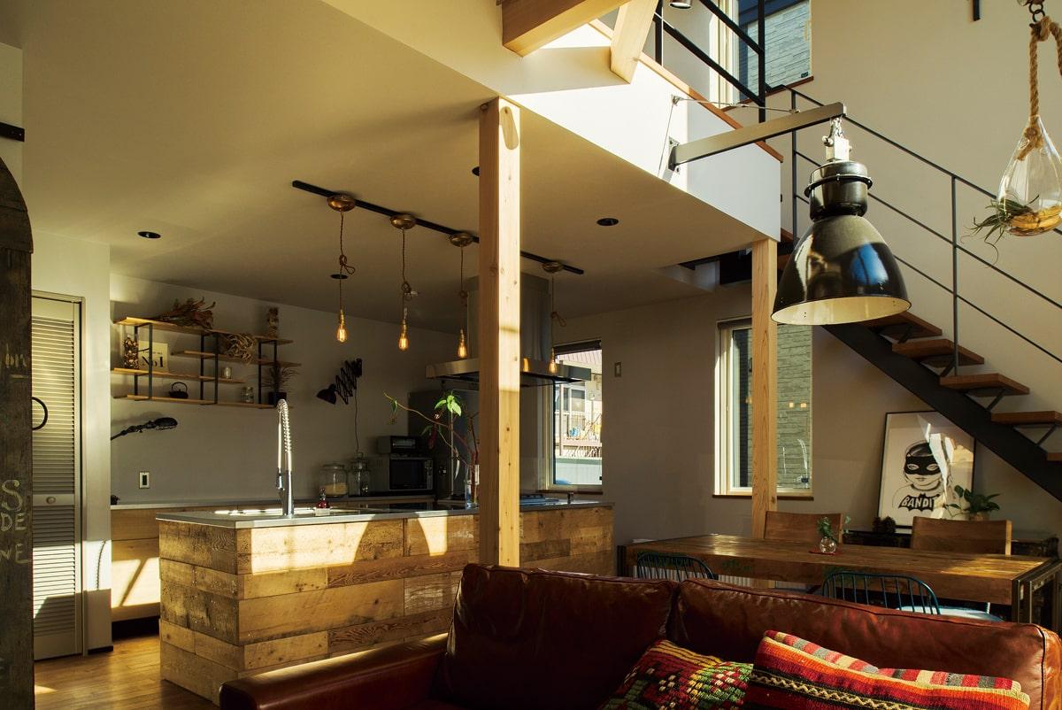 インダストリアルな雰囲気で統一されたダイニングとキッチン。木と鉄のテーブルは以前から使っていたお気に入りで、新居にもマッチ。存在感のある照明は、チェコの工場で使用されていたもの