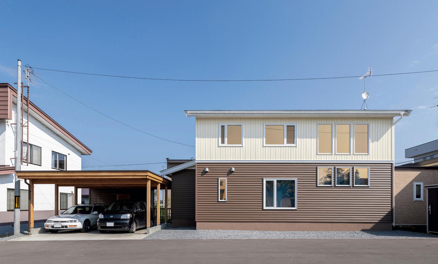 車2台収納のカーポート。外壁はアイスカフェラテ色のツートンカラー。素材は塩ビの樹脂サイディングで、耐久年数が長く、アメリカやカナダでは普及している建材