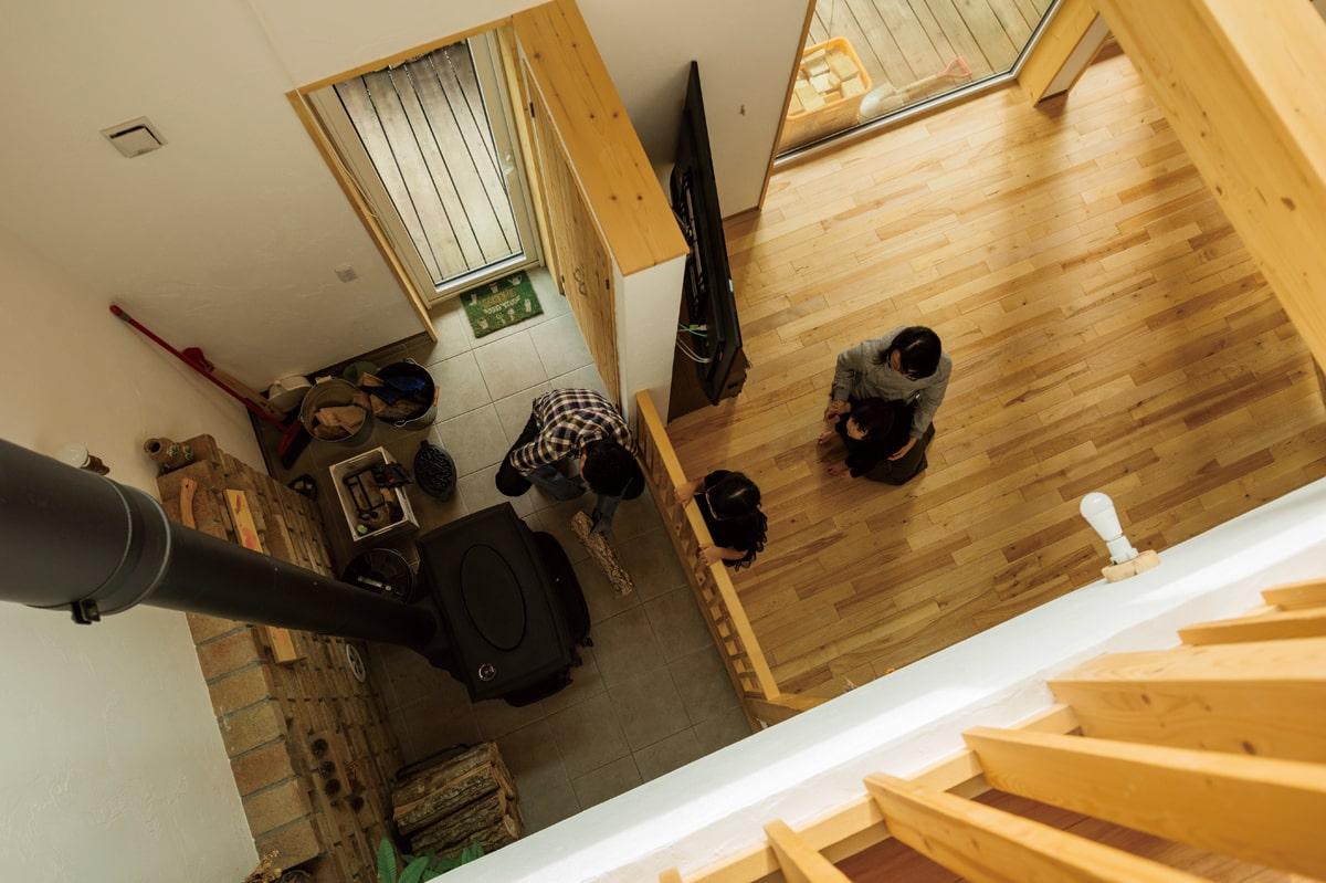 2階から吹き抜けを見下ろすとそこに薪ストーブが。火を焚き始めると、自然と家族全員が集う