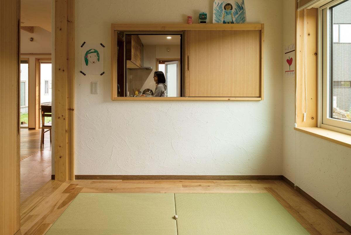 和室の小上がりからは窓を通してキッチンを覗けるつくり。畳で子どもたちを遊ばせながらも目が行き届く