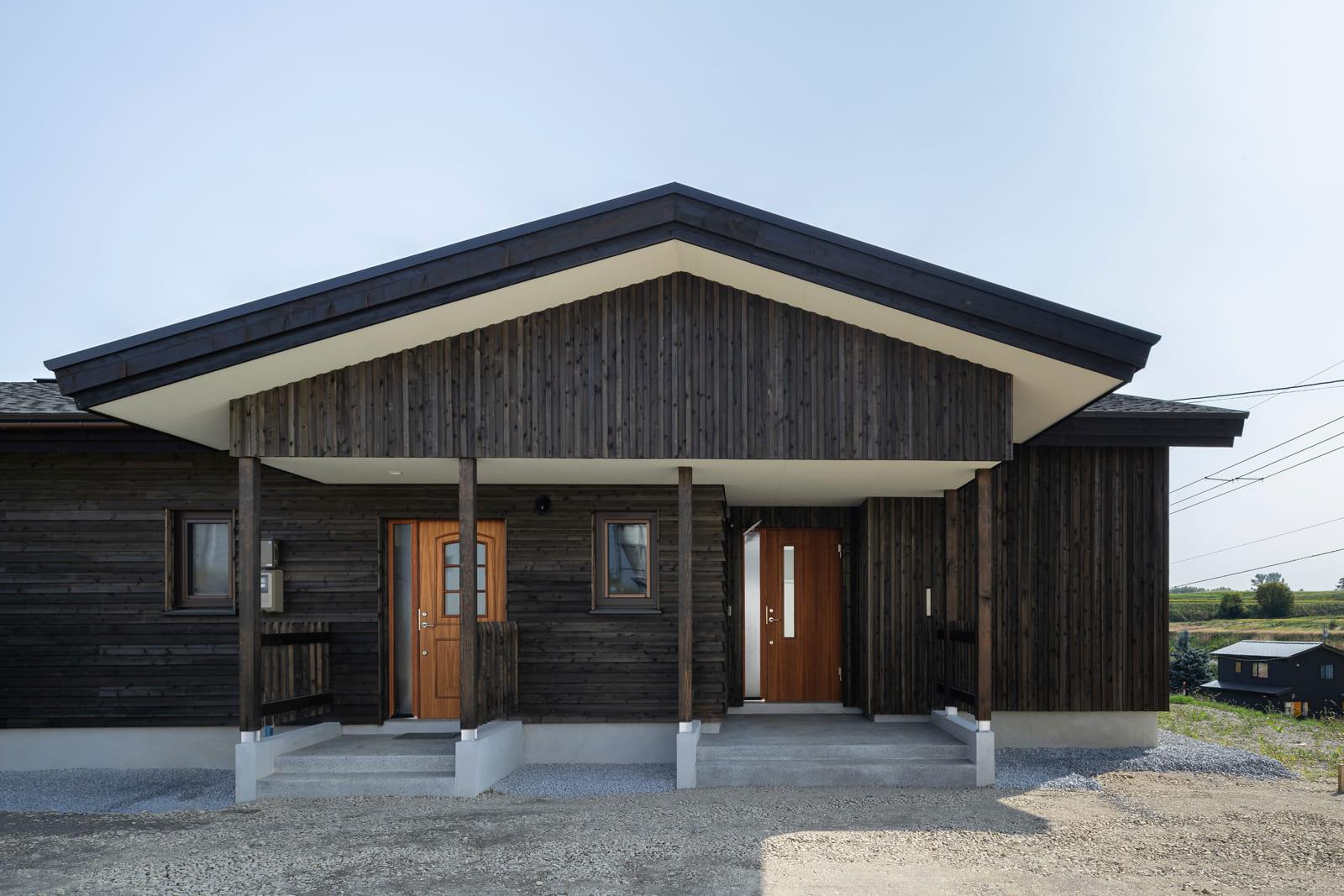三角屋根の下に2つの玄関が並ぶ。玄関(右)と裏玄関(左)でドアの色やデザインを変えアクセントに