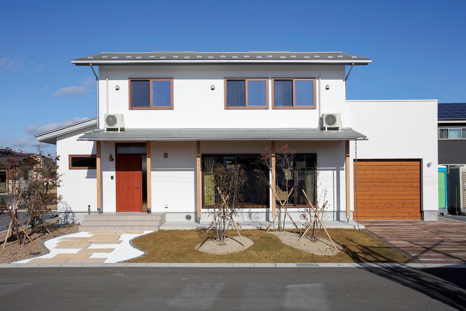 玄関ドア、ガレージのシャッターは木製で、外壁にはホタテ漆喰を施工。大きな庇屋根が夏は日陰をつくり、冬は陽射しをとり入れる