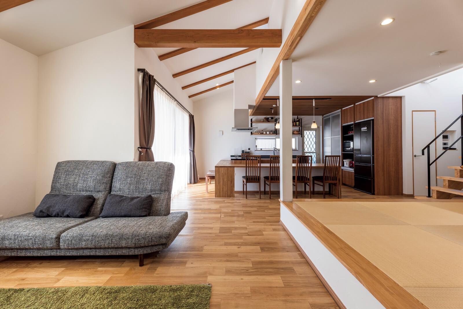 現しの梁と床の無垢材が優しい。屋根の形状を利用した勾配天井には換気用の小窓も設け、風が抜ける設計