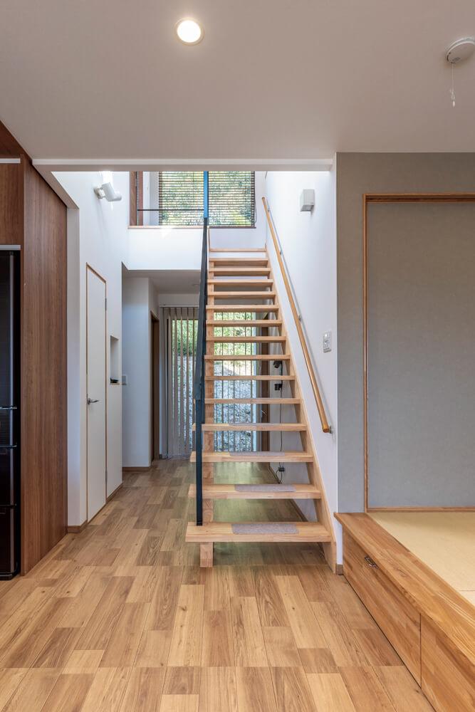 スリット階段の位置は、キッチンの前を通って2階に行く動線にした。南から北へ抜ける風の通り道も考慮