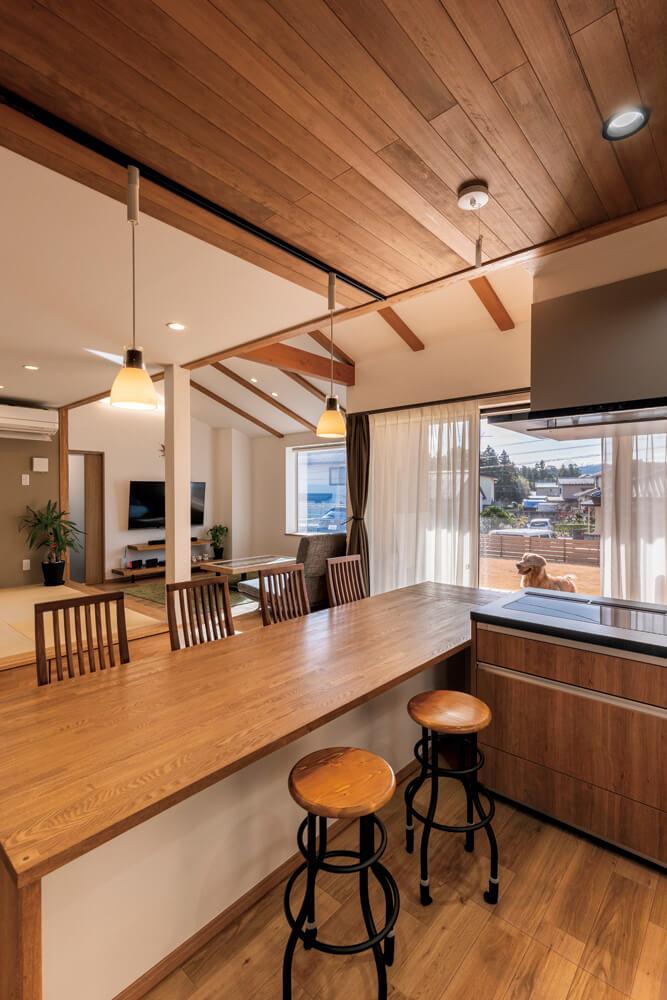 キッチンの天井は無垢の羽目板を張り、間接照明をしつらえた。ここに立つとリビングから庭まで広く見渡せる