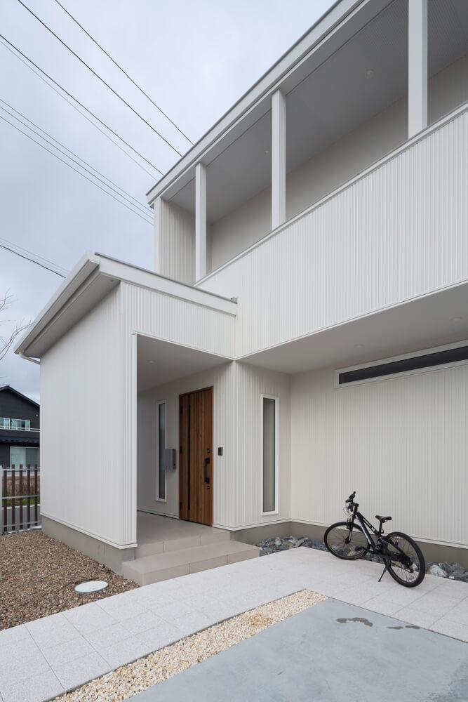 白一色のサイディングの外観が人目を惹く。屋根付きのポーチが内と外のバッファゾーンの役割を果たす