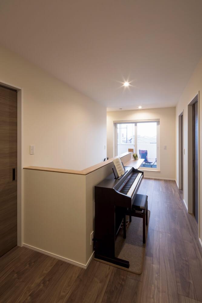 ピアノが置かれた2階ホール。奥には造作のカウンターも。最奥の窓はL字形のバルコニーに通じる