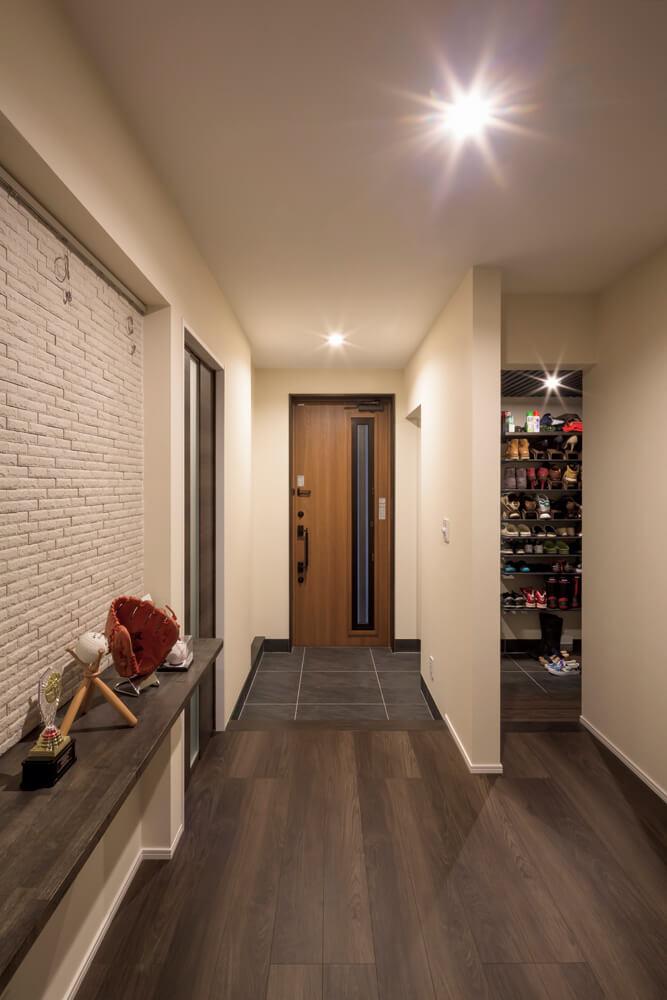 ゆとりのある玄関ホール。エコカラットの飾り棚にはお子さんたちの野球関連グッズが並ぶ