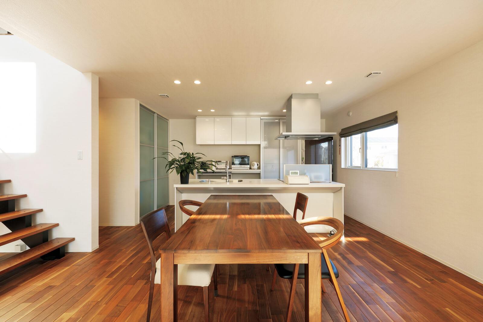 キッチンはアイランド型。床材に会わせダイニングのイスもウォールナット材で特注した。左奥、階段の裏手にトイレや洗面室などの水まわりを集約