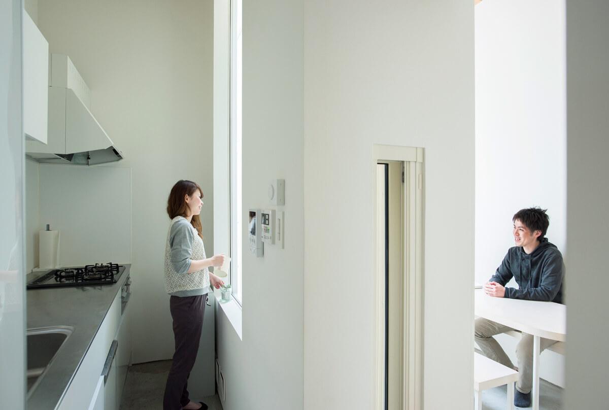 キッチンとダイニングは外部空間を挟んで窓越しに隣り合う。この距離感が心地よさを生んでいる