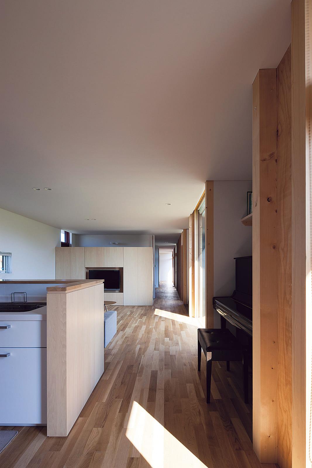 キッチンからリビング方向を見る。各室をつなぐ廊下が一直線に家の奥へと続いている