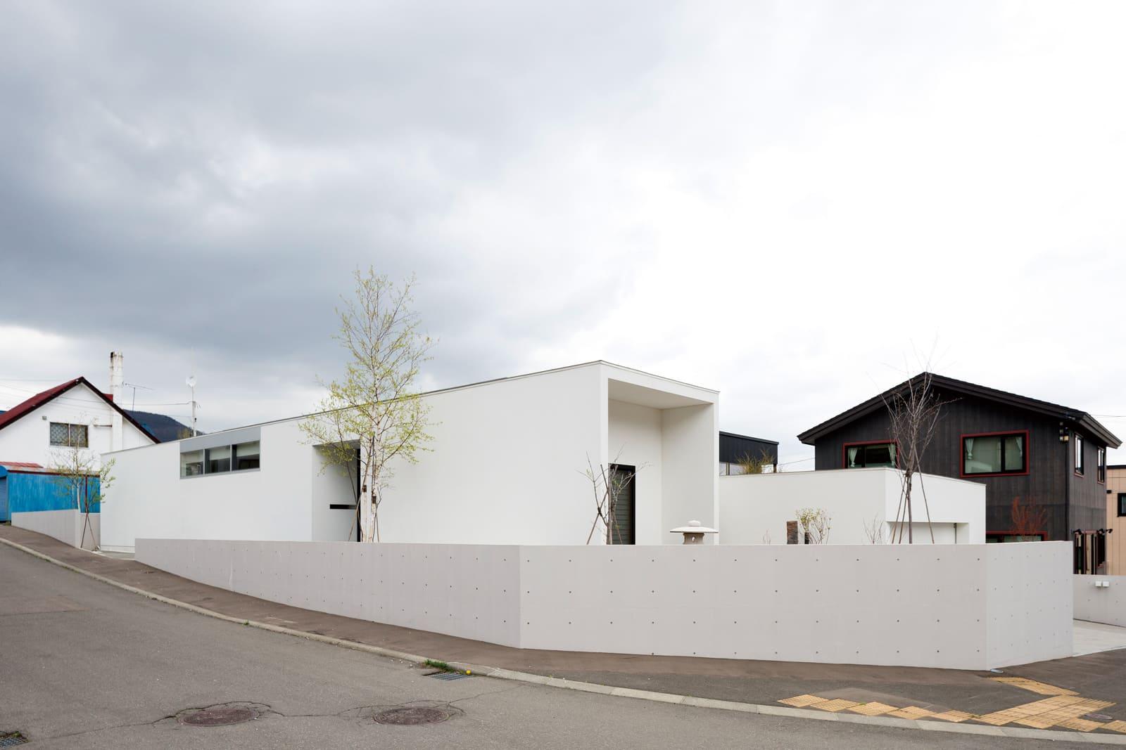建物外観は白で統一され、奥行きのある建物をより印象深くしている。道路側は高窓にすることでプライバシーと採光を確保