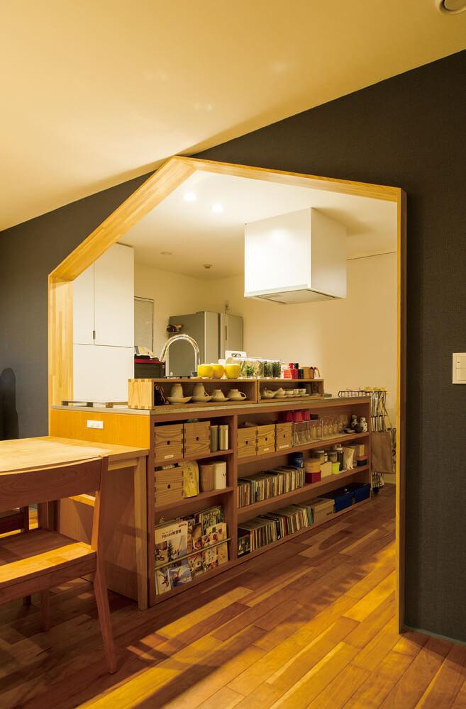 奥さんが「狭く、閉ざされた印象だった」という既存のキッチンは、木をふんだんに使った造作キッチンに変更。通路側には、ハウス型の間仕切りゲートが、開放的な家事空間のアクセントに
