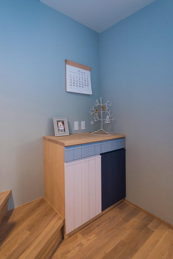 3色使いのキャビネットには、奥さん好みの雑貨が並ぶ。グラデーションカラーの壁も印象的