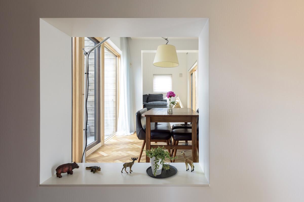 壁の一部に開けた四角い窓からリビングまでを見透せることで、空間の奥行きを演出