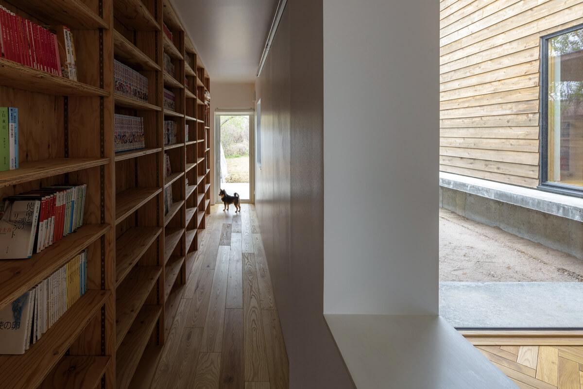 玄関を上がって左手、ダイニングテラスへとつながる廊下。片側の壁全面を使い、床から天井高までの書棚を設けた