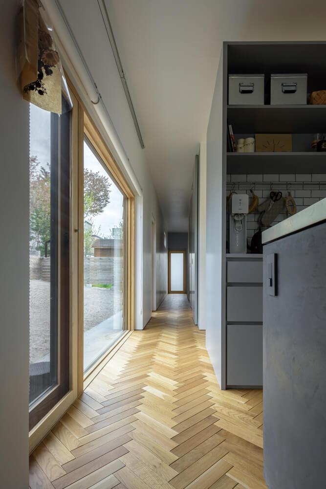 庭に沿ってキッチンから寝室へまっすぐに伸びる廊下。ヘリンボーンの床が、上質感を漂わせる