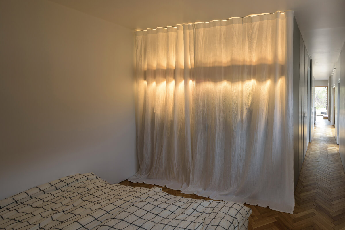扉の代わりにカーテンを設置した寝室のクローゼット。照明を灯すと、間接照明のような効果を生む
